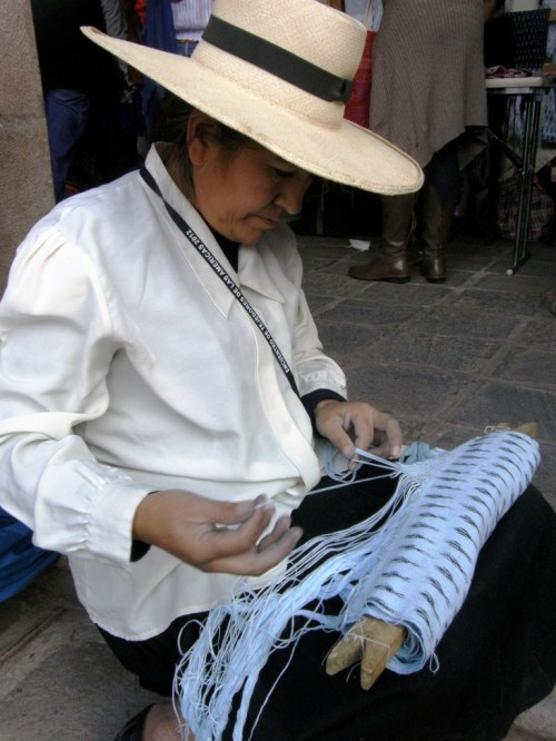 A weaver of panones of Tacabamba, Peru, puts the finshing touch on hher woven ikat shawl by knotting an intricate pattern into the the fringe.