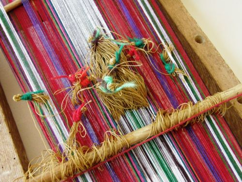 Bunches of string heddles control the colored layers of warps on the horizontal loom of Taquile Island, Peru