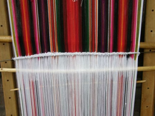 Threads are stretched on the typical leaning vertical loom of Tarabuco, Bolivia