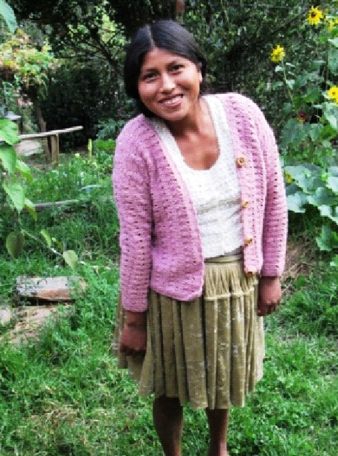"Adviana Vargas is 18 and still considered a ""chica"". Howevere, she weaves with the women's group as she lives with teh father of her 16-month old son and is expecting another child. She is showing the cardigan that she made after a visting volunteer opened up the mystery of the patterns and instructions in magazines that had been in the group's possession for years. Unitl then no onehad had the skills to read and interpret them."