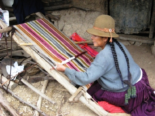 Here is Casimira Calcina working on the leaning verticalloom which is typical of the region. She lives in the rural community of Huancarani. Being widowed and with her children having migrated, she works hard alone to run her farm and tend her flock.
