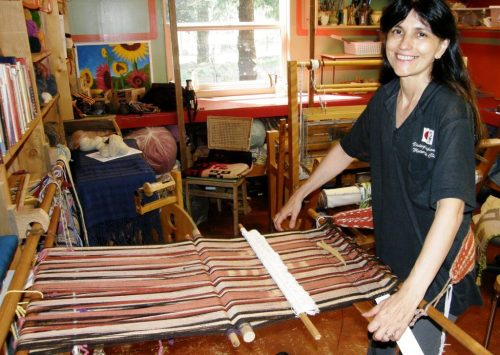 woman standing backstrap weave loom