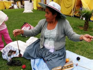 Maxima in Cochabamba adds extra twist to her handspun yarn before winding a warp for a pebble weave band.