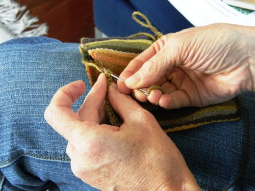 Lisa decorates the mouth of the Bolivian woven pouch, which she edged with a tubular band, with cross knit looping..a sewn technique.
