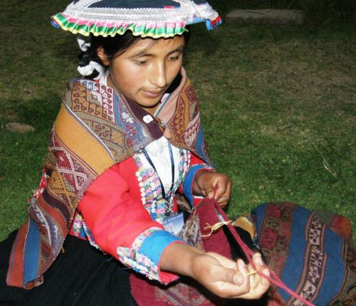 A young girl from Pitumarca weaves a plain-weave tubular band while sewing it to the edge of a piece of woven cloth.