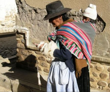 "A lady in Bolivia carries her randchild on her back leaving her hands free to spin yarn on a drop spindle. The carrrying cloth is traditionally hand woven although this lady is using a synthetic factory-made piece. These cloths are used tocarry any kind of load...goods being taken to and from market or ""luggage"" on a trip."