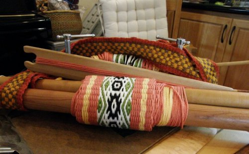 Here is Yonat's backstrap warp rolled up at the end of the day with just a couple of inches left to go. Yonat found taht weaving outdoors seated on the ground with her warp angled steeply was much more comfortable for her.