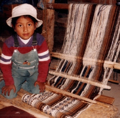 Migue Andrango's garnddaughter sits alongside one of the pieces in progress in his workshop in Peguche, Ecuador.