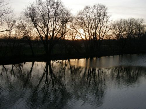 The ast rays of the setting sun over the creek at The Mannings Handweaving Studio in Pennsylvania.