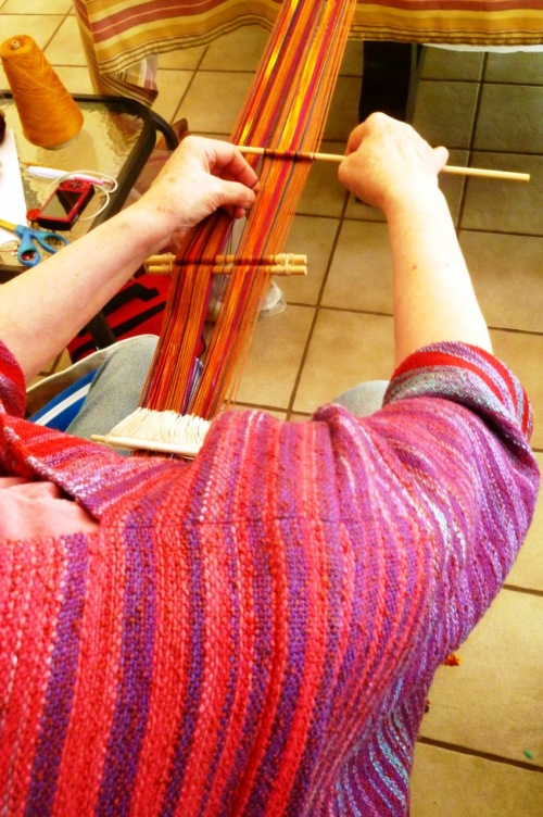 Thse who were weaving plain-weave pieces, like Sara, here, inserted a coil rod to prevent corregation. Sara is ising reeld silk that she dyed herself and inserted two hand-painted sections.