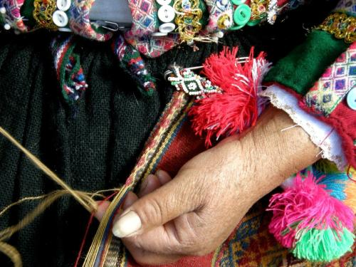 A weaver from Pitumarca weaving and sewing a tubular band edging