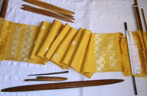 finished yellow scarf on loom with tools